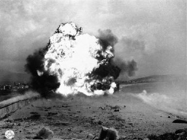 An explosion flashes as mines go off when the 540th engineers group blows an entry through an anti-tank wall with teller mines at ST. Raphael in southern France on August 31, 1944. (AP Photo)