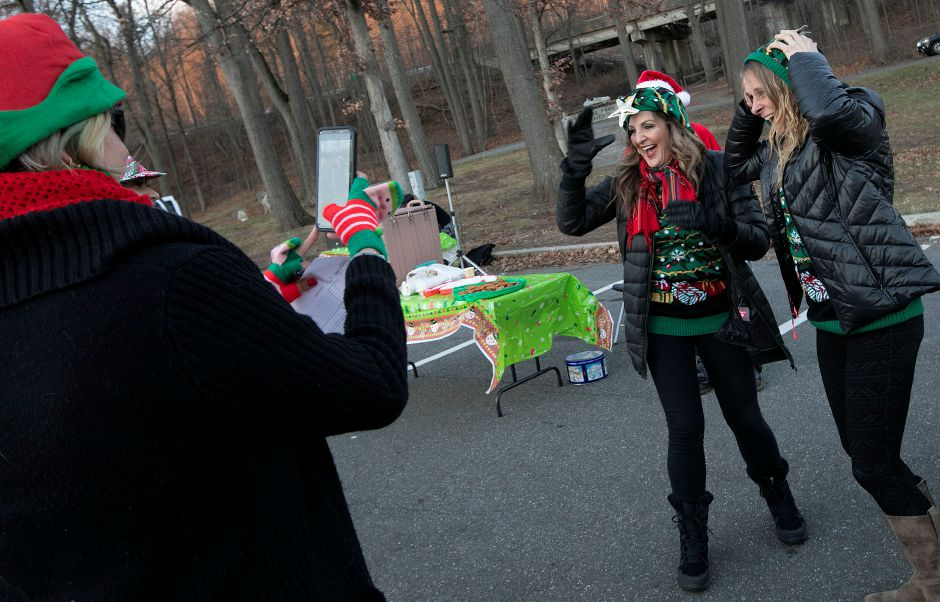 Meriden Parks and Recreation Coordinator Kathy Matula, left, snaps a photo of Pamela Fuschino, facilities coordinator, center, and volunteer, Carrie Teele, of Meriden, during a Parks and Recreation Department hosted ugly holiday sweater party at Hubbard Park in Meriden Fri., Dec. 7, 2018. Dave Zajac, Record-Journal