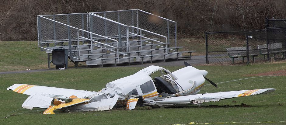 The wreckage of a small plane rests on the ball field at Wilcox Technical High School in Meriden, Fri., April 12, 2019. The Federal Aviation Administration and the National Transportation Safety Board are investigating after the Thursday crash. Two men suffered minor injuries, police said. Dave Zajac, Record-Journal