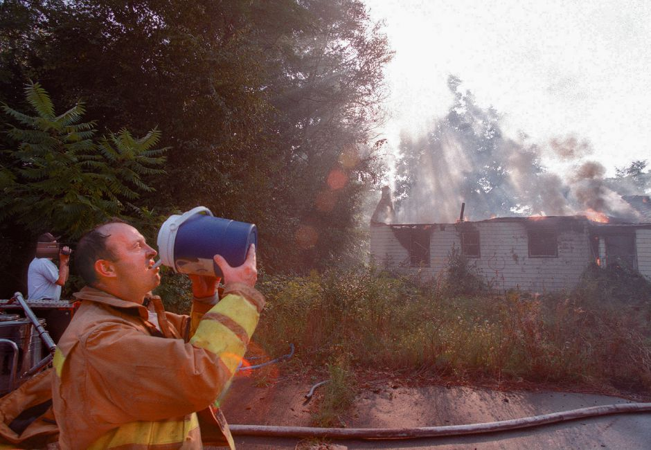 RJ file photo - Southington Fire Capt. David Mikosz takes a quick water break as firefighters put out a fire at an abandoned home on Queen Street Sept. 6, 1998.