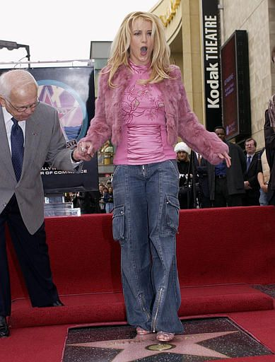 Pop star Britney Spears steps onto her new star with an assist from Johnny Grant, honorary mayor of Hollywood, as she is honored with the 2,242nd star on the Hollywood Walk of Fame, Monday, Nov. 17, 2003, in Los Angeles. (AP Photo/Nick Ut)