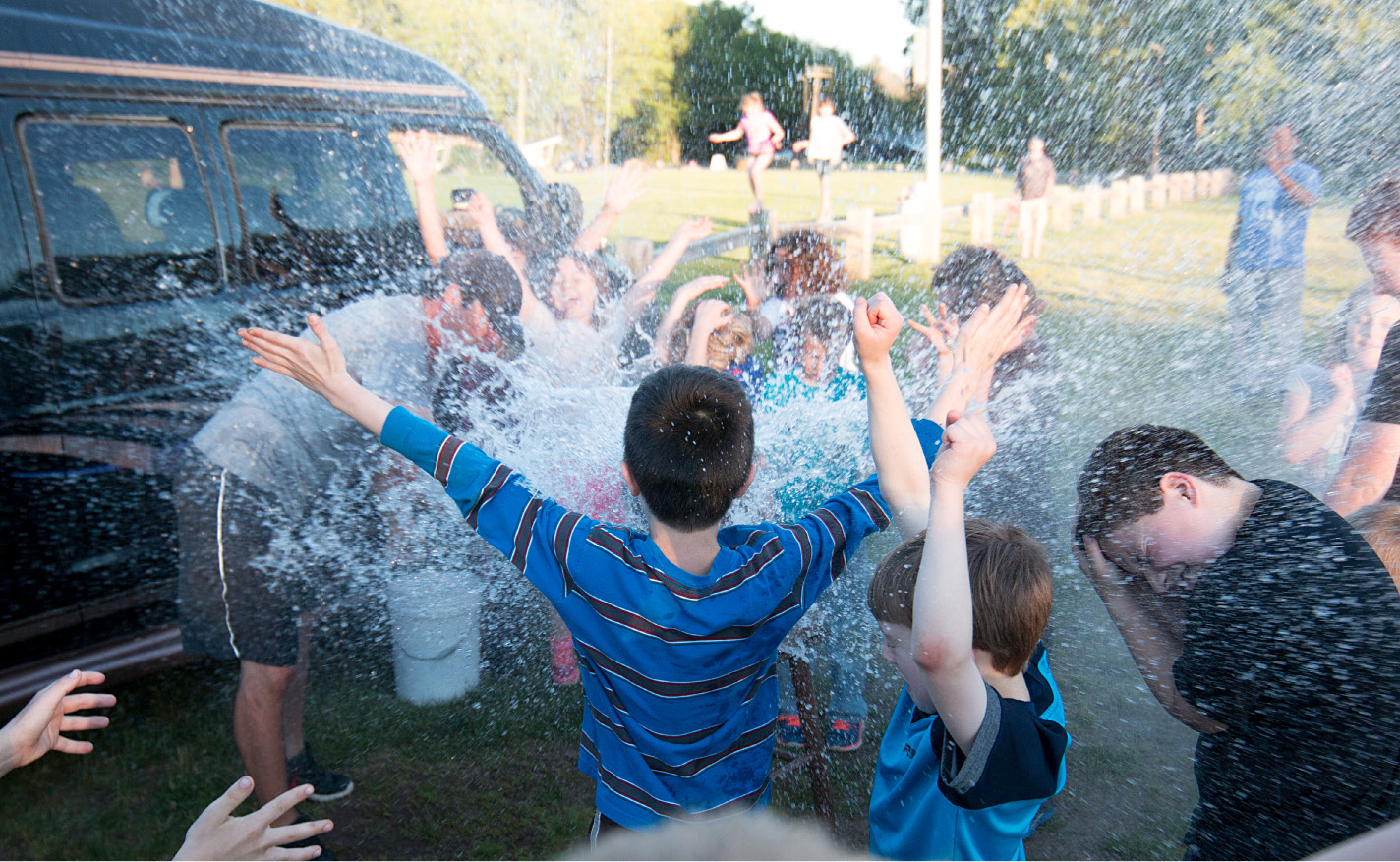 Kids are splashed by a water balloon smashed by Southington physical education teacher Eric Korp at the Southington Drive-In