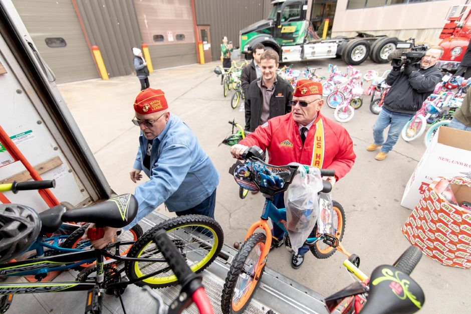 James Morris, right, commandant of the Hardware City Detachment of the Marine Corps League, loads bikes into a truck after Manafort Brothers Inc donated 100 bikes to the Marine Reserves Toys for Tots program on Dec. 12, 2018. | Devin Leith-Yessian/Plainville Citizen