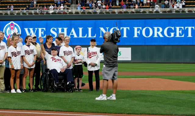 Tom Barnett Sr., in wheelchair, waves as the family was recognized during a tribute to 9/11 prior to a baseball game between the Minnesota Twins and the New York Yankees, Tuesday, Sept. 11, 2018, in Minneapolis. Tom Barnett Jr. was aboard Flight 93 which went down in Pennsylvania. (AP Photo/Jim Mone)