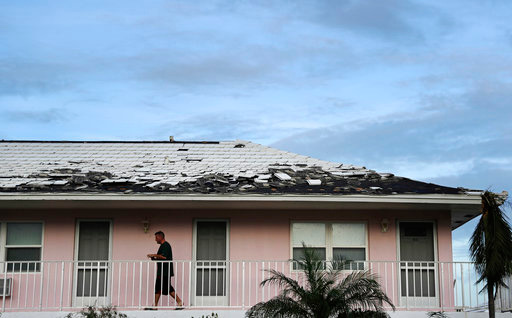Tony Loduca walks back to his apartment past a roof whose tiles where torn off from Hurricane Irma in Marco Island, Fla., Monday, Sept. 11, 2017. (AP Photo/David Goldman)