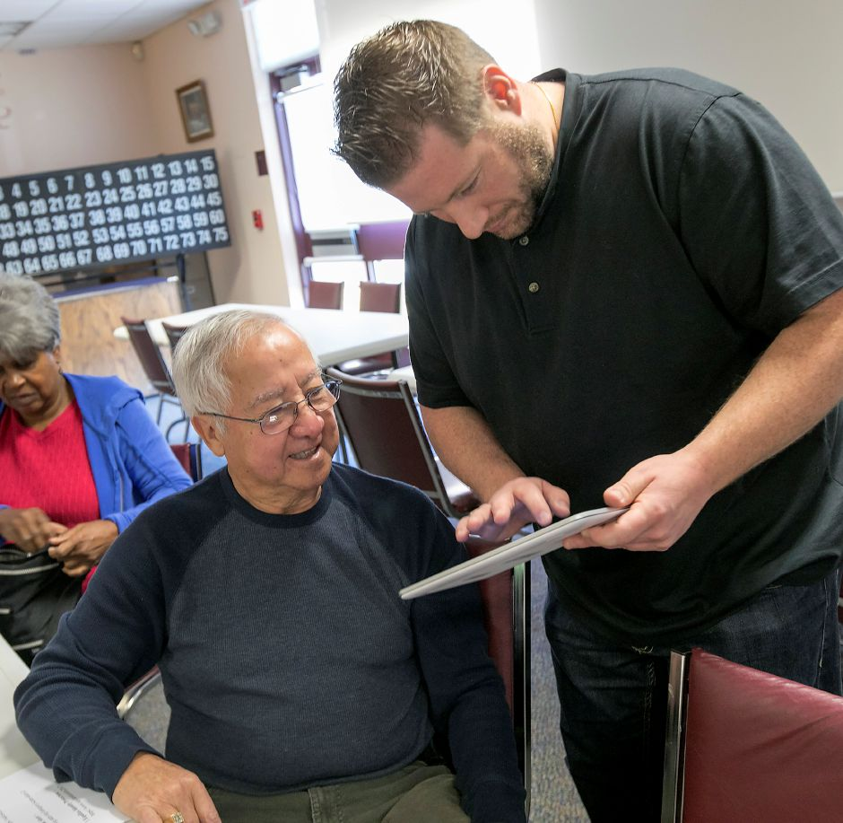 Quinnipiac University computer information systems student Steve Koch helps Gus Trujillo, of Wallingford, on his tablet during a cyber security workshop at Wallingford Senior Center, Wednesday, Nov. 29, 2017. Dave Zajac, Record-Journal