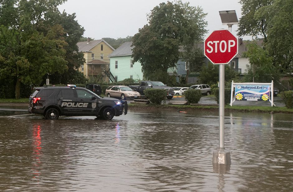 Meriden police block the intersection of Pratt and Mill Streets, Tuesday, Sept. 25, 2018. Heavy rain Tuesday evening closed roads and flooded basements of local homes. Dave Zajac, Record-Journal