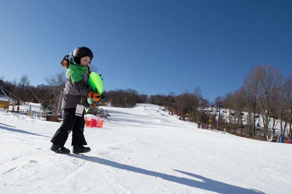 Ben Raver-Shvetz, 8, of Sandy Hook, carries his snow board to the lift Friday at Mount Southington in Plantsville. Dec. 29, 2017 | Justin Weekes / Special to the Record-Journal