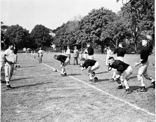 Assistant coach Vince Lombardi, left, looks over three center and three quarterbacks during football practice at the U.S. Military Academy, West Point, N.Y., Aug. 29, 1951.  (AP Photo/John Rooney)