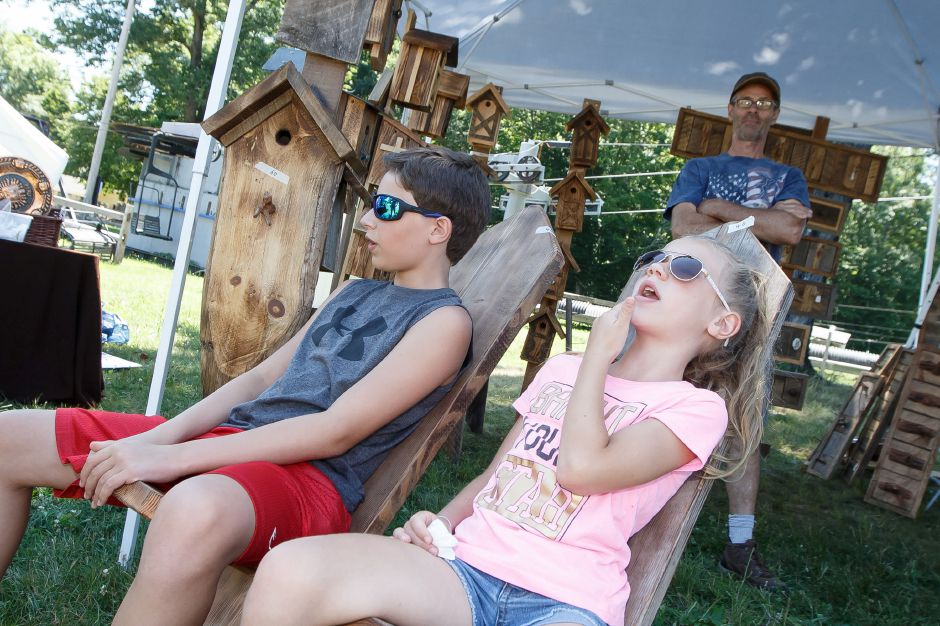 Gavin Mattison 12 and sister Lexie 8 try out hand built chairs from Ridgewood Bird Barn Sunday during the Mountainside Market at Powder Ridge Mountain Park and Resort in Middlefield  July 8, 2018 | Justin Weekes / Special to the Record-Journal