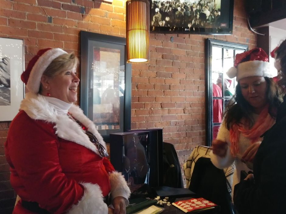 Carol Sadlowski and April Ryczak greet guests at Gaetano's during SantaCon in downtown Wallingford. Saturday, December 8, 2018. Jeniece Roman. Record-Journal