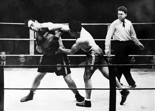 Primo Carnera, former world champion, attempted to come-back in a fight with the Marseilles champion, De Meglio, at the Salle de Wagram, Paris, on Nov. 19, 1937. He was beaten on points. Carnera registers pain when De Meglio scores with a right to the chin. (AP Photo)