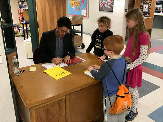 "David Wenzel signs copies of his book ""They All Saw a Cat"" for Lyman students during his visit on March 24. 