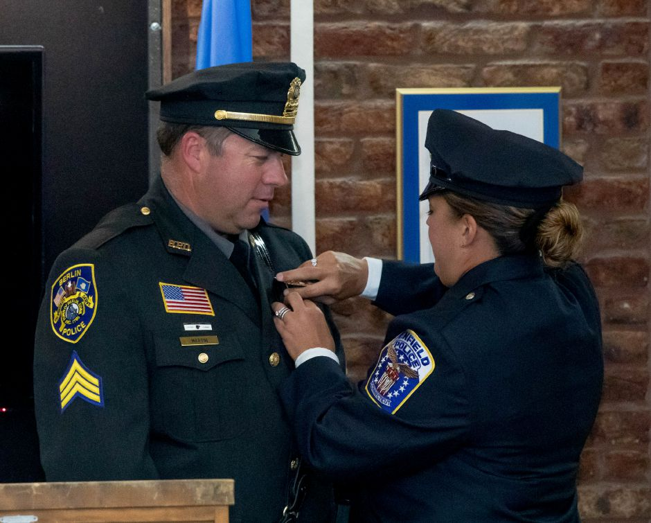 Berlin Police Sergeant Rob Martin has his badge pinned to his uniform by his wife, Sherri Martin, during his promotion ceremony on August 26, 2019. | Devin Leith-Yessian/Berlin Citizen