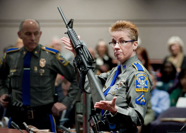 FILE - In this Jan. 28, 2013, file photo, firearms training unit Detective Barbara J. Mattson, of the Connecticut State Police, holds a Bushmaster AR-15 rifle, the same make and model used by Adam Lanza in the 2012 Sandy Hook School shooting, during a hearing at the Legislative Office Building in Hartford, Conn. A divided Connecticut Supreme Court ruled that gun maker Remington can be sued over how it marketed the Bushmaster rifle used in the massacre. In court documents filed Friday,...