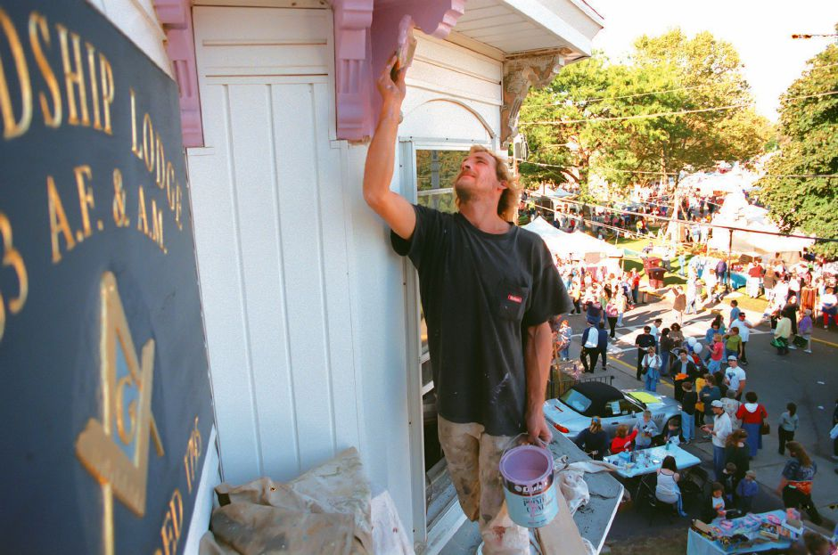RJ file photo - Joe Maxfield of Bristol paints the scrolls on teh eaves of the Friendship Lodge No. 33 as the Southington Apple Harvest Festival winds up Oct. 11, 1998.