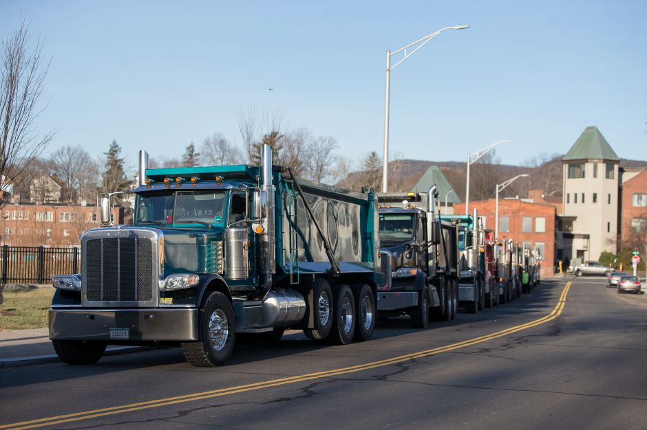 Dump trucks line Mill Street waiting to haul away debris of the last Mills Apartment building Thursday in Meriden December 27, 2018 | Justin Weekes / Special to the Record-Journal