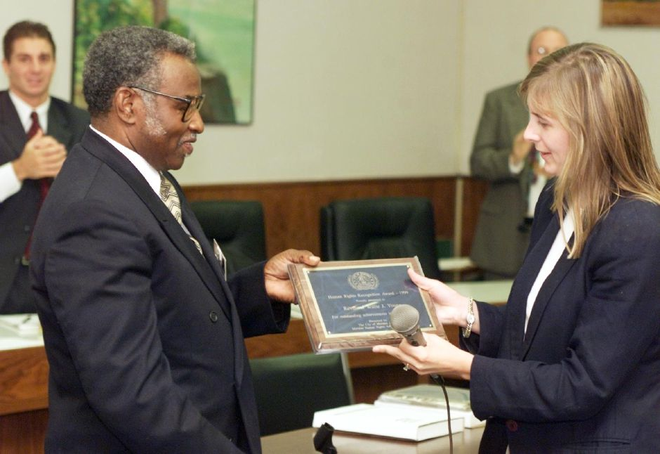 The Rev. Willie Young receives a human rights award from human rights advocate Deborah Moore Mon., July 17 at City Hall.