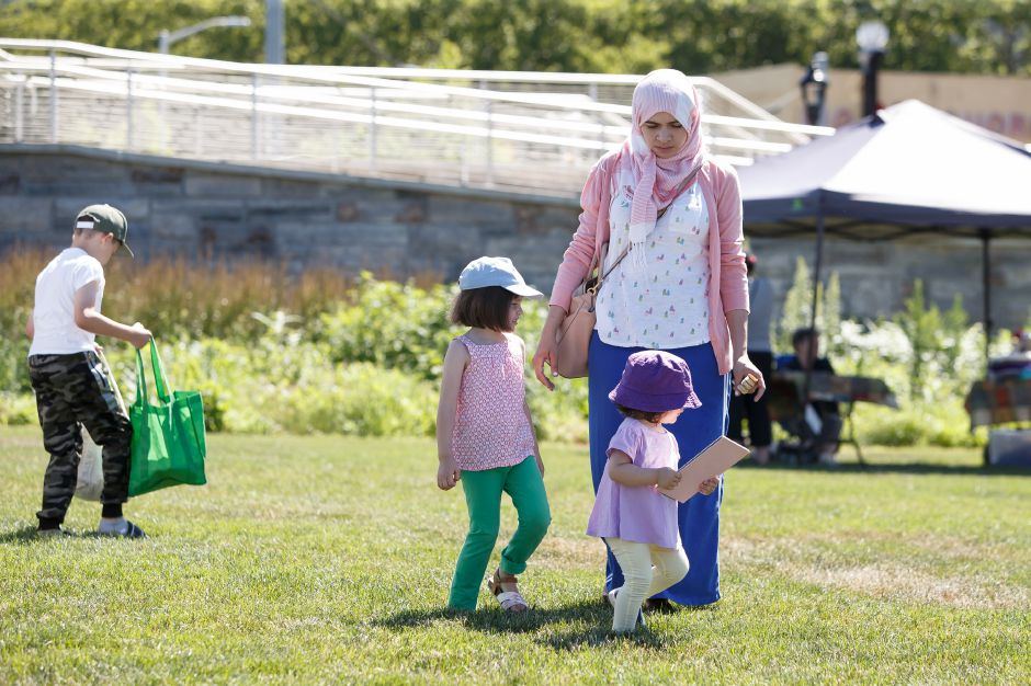 Amina Gjonbalaj with her daughters Selma 4 and Leena 1 of Meriden walk the market Saturday during the Meriden Farmers Market at the Meriden Green in Meriden July 7, 2018 | Justin Weekes / Special to the Record-Journal