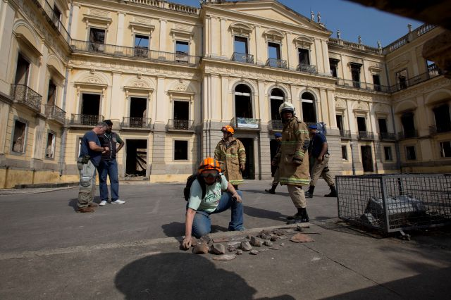 A National Museum worker organizes pieces rescued from the museum after an overnight fire in Rio de Janeiro, Brazil, Monday, Sept. 3, 2018. A huge fire engulfed Brazil