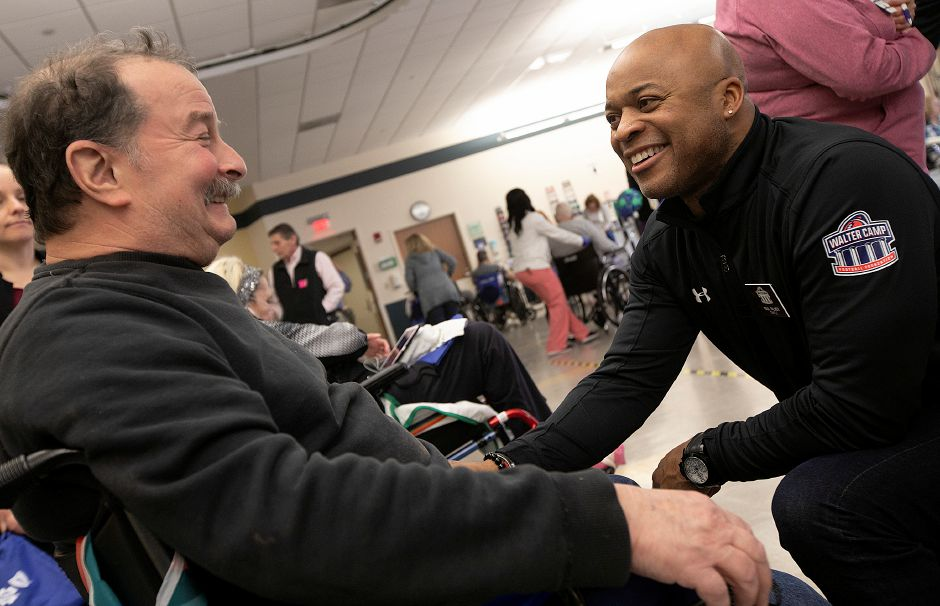 Paul Palmer, right, visits with patient Paul Sandri, of Naugatuck, during the Walter Camp Football Foundation event at Gaylord Hospital Friday. Palmer was a Temple 1986 WCFF All-American running back. Dave Zajac, Record-Journal