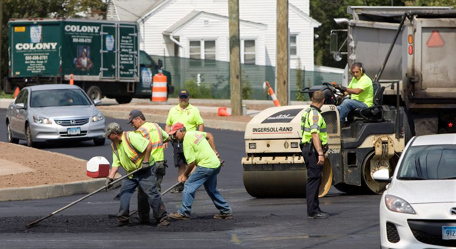 Paving crews resurface the intersection of Liberty Street and Gravel Street in front of Maloney High School, Tuesday, August 25, 2015. | Dave Zajac / Record-Journal
