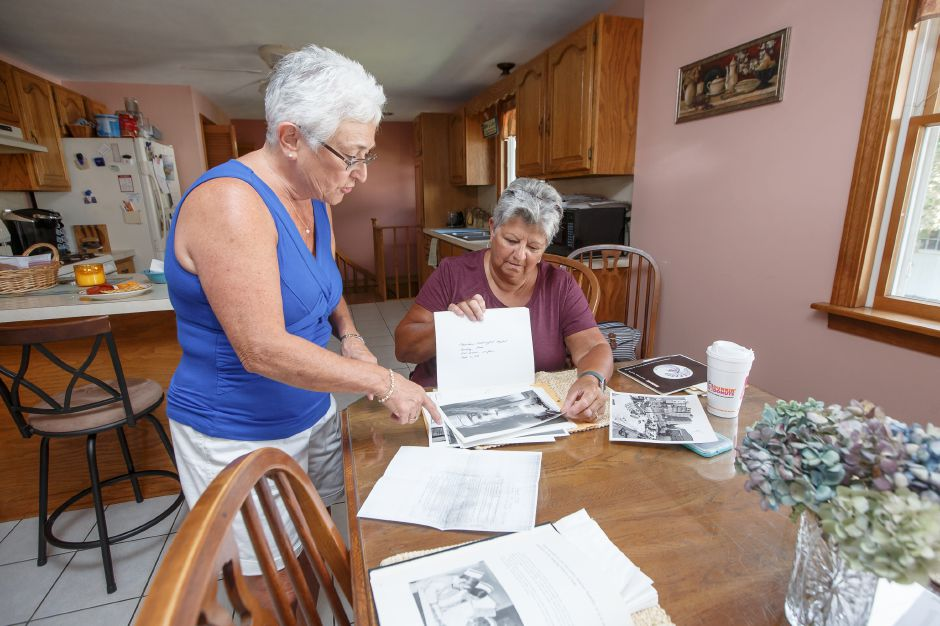 Arlene Hamelin, left, and Gerry Pierce flip through old yearbooks as they organize a reunion of former employees of Meriden-Wallingford Hospital at the Hamelin home in Meriden, Sept. 4, 2018 | Justin Weekes / Special to the Record-Journal.
