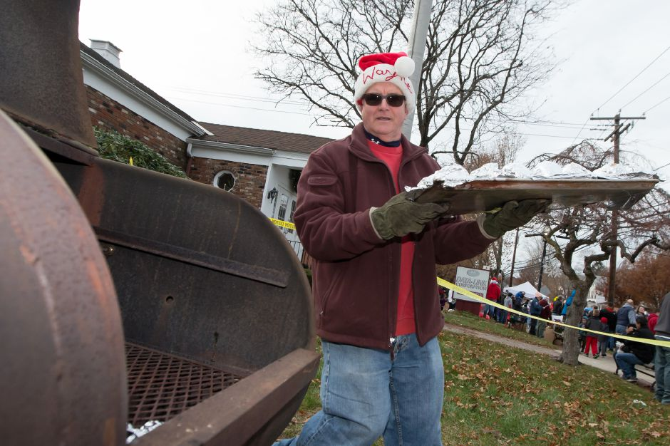 Wayne Ives carries wrapped apple to cook on a grill Saturday during Christmas in the Village on Main Street in South Meriden December 2, 2017 | Justin Weekes / For the Record-Journal