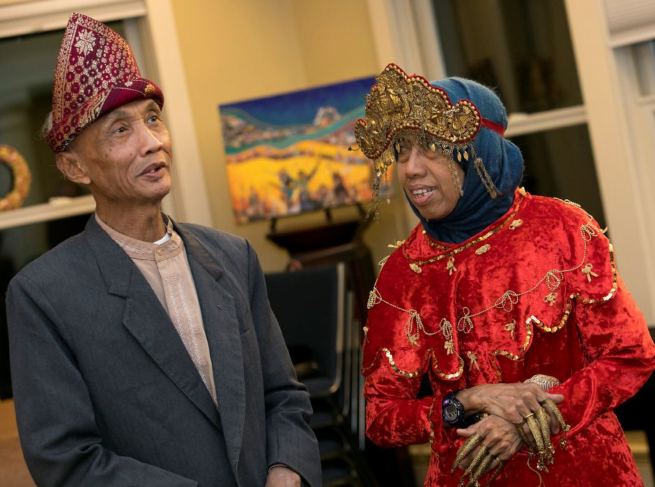 Sujitno Sajuti smiles with wife, Dahlia, who wears festive Indonesian clothing during a celebration of his 69th birthday at the Unitarian Universalist Church on Paddock Avenue in Meriden, Wednesday, Dec. 13, 2017. Sajuti, an undocumented West Hartford resident, has taken up sanctuary at the Unitarian Universalist Church. Dave Zajac, Record-Journal