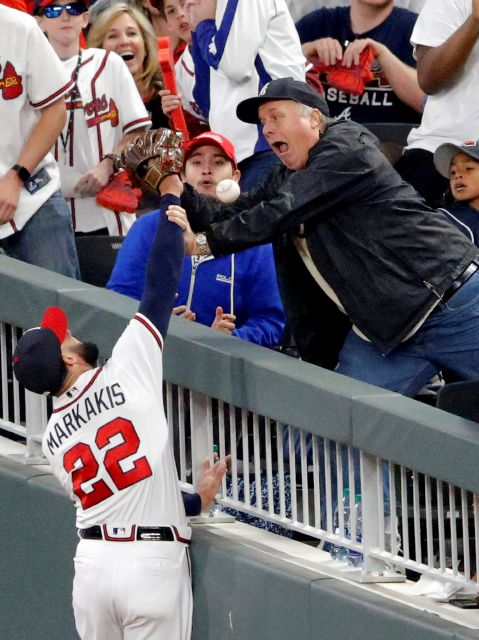 A fan interferes with Atlanta Braves right fielder Nick Markakis (22) who tries to catch a foul ball by New York Mets