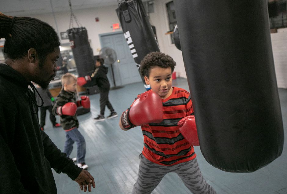 Cardiere Martin, 12,  throws a few punches as Tim Gary, volunteer youth coach, instructs at Beat The Street Community Center in Meriden on Monday. Photos by Dave Zajac, Record-Journal