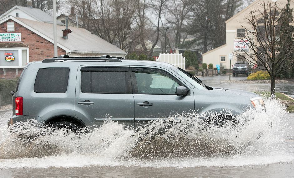 A motorist travels through a flooded section of West Main Street in Cheshire, Monday, April 16, 2018. Dave Zajac, Record-Journal