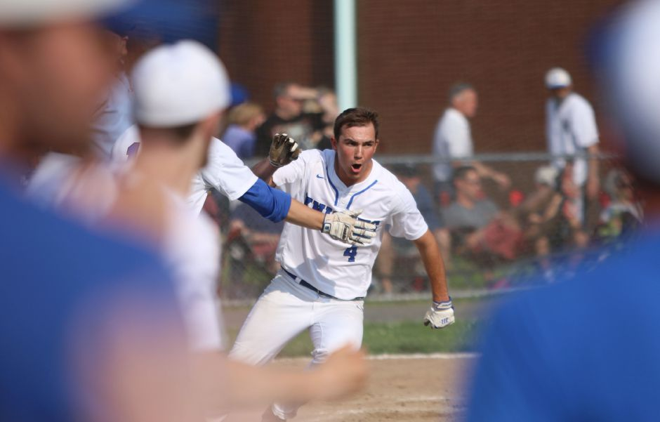 Southington's Andrew Paradis scored the game-winning run against Darien before running to mob Billy Carr with the rest of his teammates (below).
