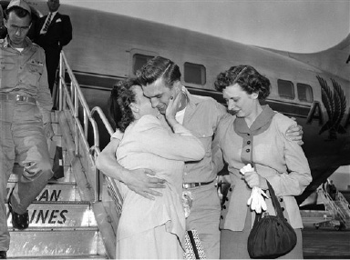 Robert W. Toth and his mother, Nettie Mertz of Pittsburgh, embrace at the airport in Washington, Aug. 22, 1953, after he arrived from Korea. He has one arm around his sister, Audrey Toth, also of Pittsburgh. Toth has arrived for a federal hearing to test the legality of the law under which the Air Force arrested him as a civilian and flew him to Korea on a murder charge. Toth, a former airman first class, is charged with the murder of a Korean civilian. (AP Photo/Charles Gorry)