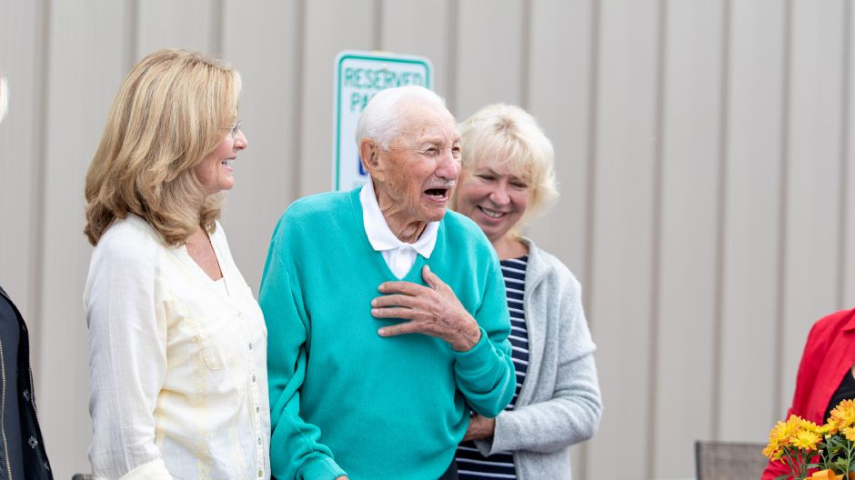 Michael Budney, in blue, celebrated his 107th birthday at the aerospace manufacturing plant he opened over 30 years ago. He continues to visit every day. | Devin Leith-Yessian/Berlin Citizen