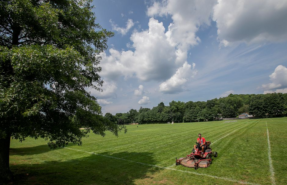 Parks and Recreation summer helper, Quinn Boucaud, 19, mows the soccer field at Bartlem Park in Cheshire, Friday, August 10, 2018. Richard Bartlem, the town's first parks department director and the namesake for Bartlem Park, is being remembered an active member of the local community. Bartlem died on Aug. 2 at 90 years old. Dave Zajac, Record-Journal