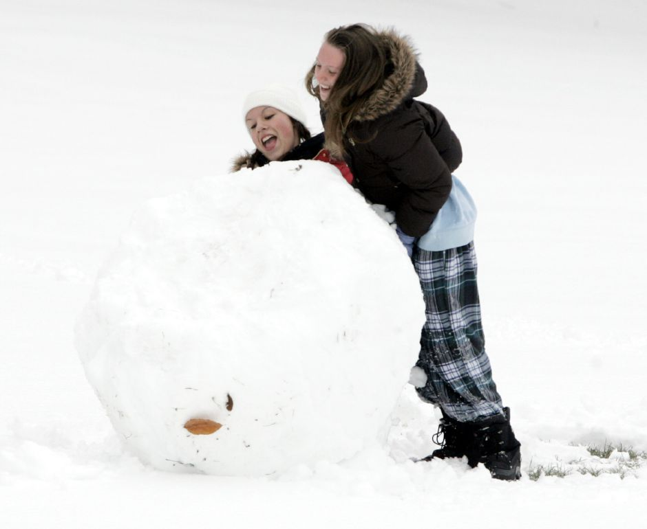 Alica Cruz, 14, left, and Stephanie Adanowicz, 14, right, try and push a giant snowball behind Nathan Hale School in Meriden on Jan. 14, 2008. The sticky snow was good for making snowmen and snow balls.