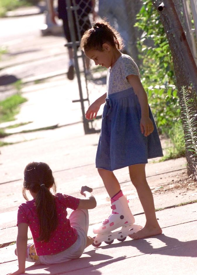 Jaryann Suarez ,7, right, shares one of her rollerblades with cousin Ivonne Barriera,6 as they learn to skate outside Jaryann