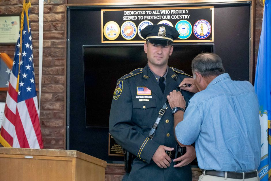 Berlin Police Lieutenant Shawn Solek has his badge pinned to his uniform by his father, John Solek, during his promotion ceremony on August 26, 2019. | Devin Leith-Yessian/Berlin Citizen