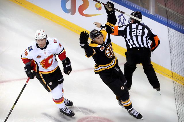 Jake DeBrusk (74) of the Boston Bruins, right, celebrates next to James Neal (18) of the Calgary Flames after scoring a goal during the first period of their 2018 NHL China Games hockey game in Beijing, China, Wednesday, Sept. 19, 2018. (AP Photo/Mark Schiefelbein)