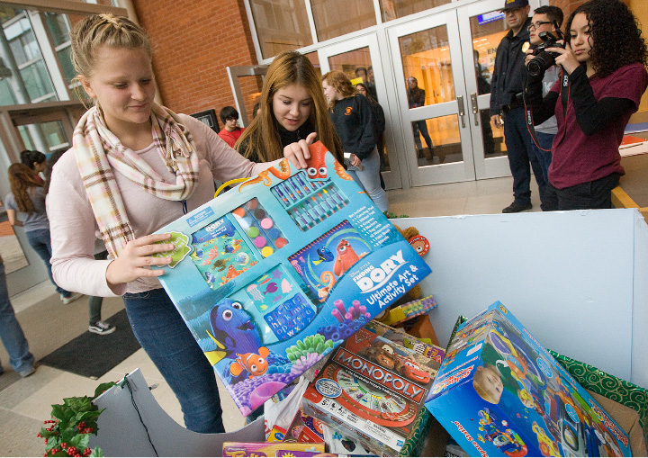 Students, Katie Gaedeke, 14, far left, and Alex Nissle, 14, add toys to a collection box during Wilcox Tech