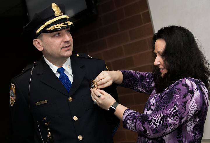 Newly promoted Deputy Chief Mark Walerysiak wears his new badge with help from his wife, Michelle, during a swearing-in ceremony Wednesday at the Meriden police station.| Dave Zajac, Record-Journal