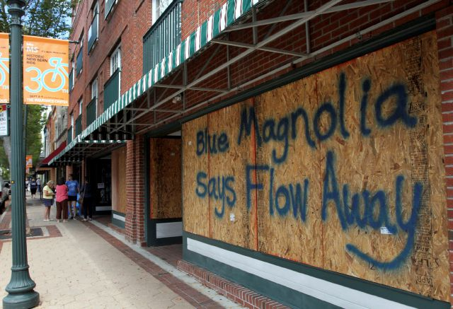 Storefronts have wood paneling installed over windows, Tuesday, Sept. 11, 2018, in New Bern, N.C., as a precaution against storm damage from Hurricane Florence. (Gray Whitley/Sun Journal via AP)