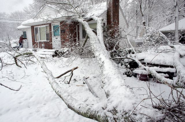 Brian Farrell, of Walpole, Mass., left, enters his home Thursday, March 8, 2018, after a tree fell on the house and a car, right, in Walpole. For the second time in less than a week, a storm rolled into the Northeast with wet, heavy snow Wednesday and Thursday, grounding flights, closing schools and bringing another round of power outages to a corner of the country still recovering from the previous blast of winter. (AP Photo/Steven Senne)