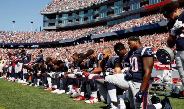 FILE - In this Sept. 24, 2017 file photo, several New England Patriots players kneel during the national anthem before an NFL football game against the Houston Texans in Foxborough, Mass.  Patriots fans have burned team gear in protest after a number of players kneeled during the national anthem before last weekend