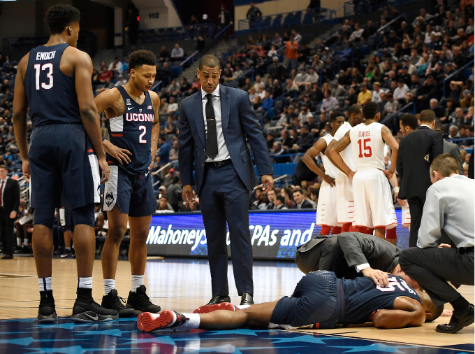 Connecticuts Rodney Purvis, right is tended to by trainer James Doran as head coach Kevin Ollie, center, and players Steven Enoch, left, and Jalen Adams, look on during the first half of an NCAA college basketball game against Houston in the American Athletic Conference tournament quarterfinals, Friday, March 10, 2017, in Hartford, Conn. Purvis collided with another player. (AP Photo/Jessica Hill)