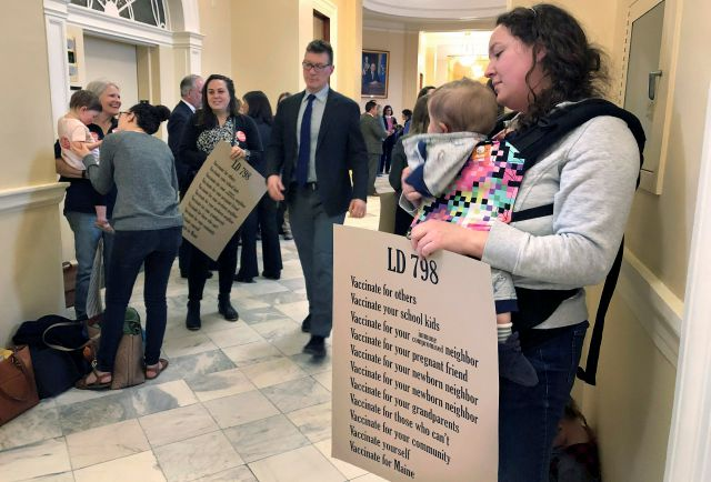Kate Herrold, of Falmouth, holds her daughter with other mothers in a hallway, Thursday, May 2, 2019, at the Statehouse in Augusta, Maine, where the Senate passed a bill ending non-medical vaccine exemptions. The bill would end religious and philosophical opt-outs by 2021 for public school students, as well as employees at nursery schools and health care facilities. It faces further legislative action in both chambers. (AP Photo/Marina Villeneuve)