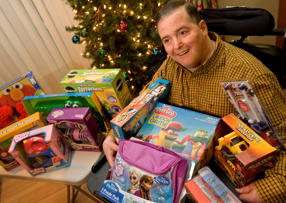 Tim Kenney, 52, of Wallingford, shows toys he purchased for Toys for Tots while at his group home in Wallingford, Monday, Dec. 14, 2015. Kenney, who has cerebral palsy, collects and cashes in recyclables to buy toys for the annual Toys for Tots event at Gaetano's Tavern on Main in Wallingford. The event this year is from 5:30- 8:30 p.m., Thursday, Dec. 17. | Dave Zajac / Record-Journal