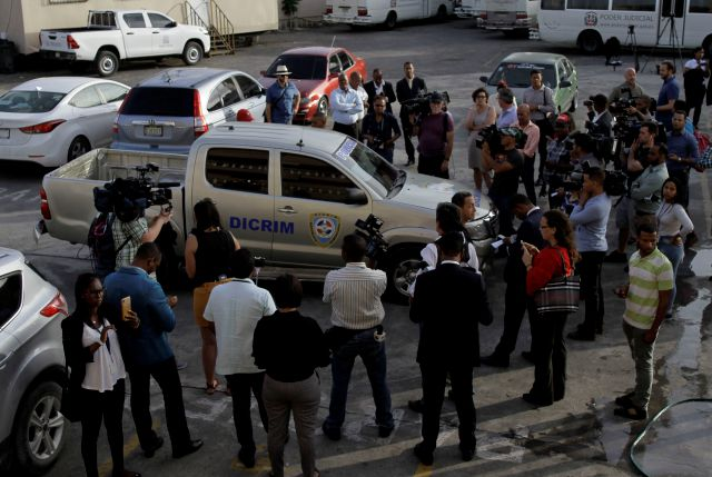 Journalists surround the police vehicle carrying Eddy Vladimir Féliz Garcia who was taken into custody in connection with the shooting of former Boston Red Sox slugger David Ortiz, as he is taken to court in Santo Domingo, Dominican Republic, Tuesday, June 11, 2019. His lawyer, Deivi Solano, said Féliz Garcia had no idea who he'd picked up and what was about to happen, and that he expected Féliz Garcia would be charged as an accomplice to an attempted murder. (AP Photo/Roberto Guzman)