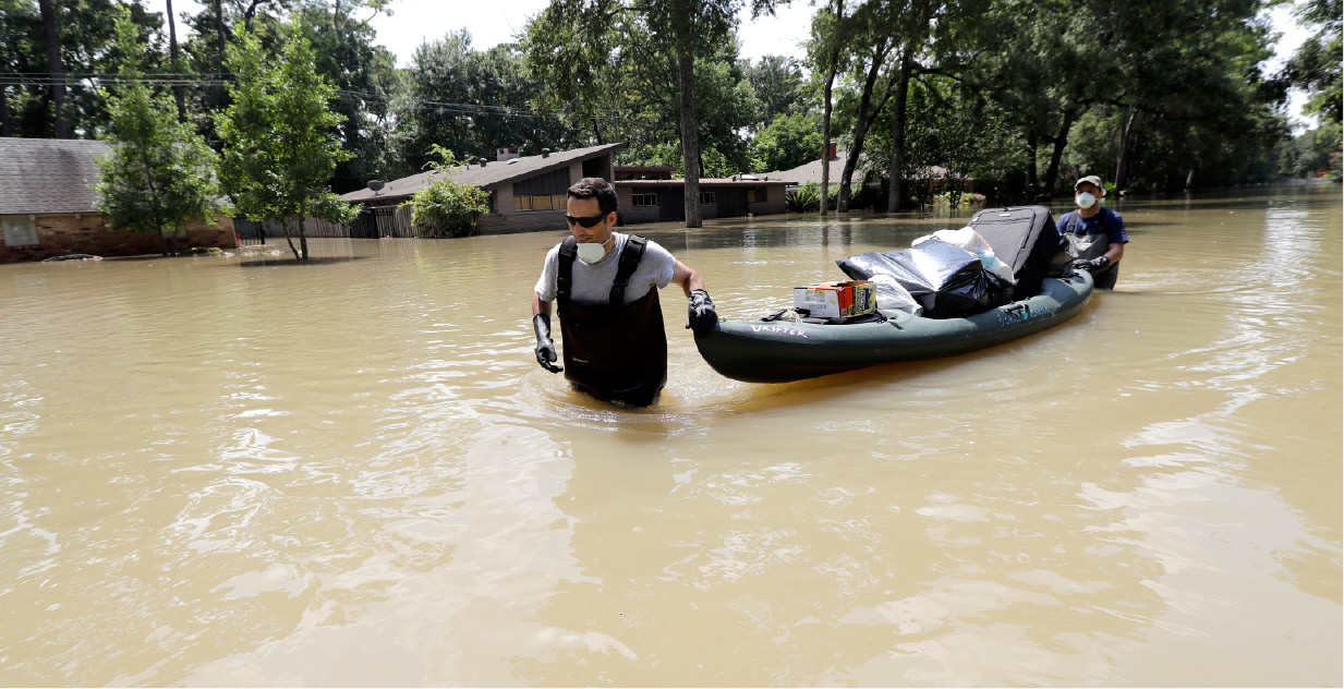 Gaston Kirby, left, is helped by friend Juan Minutella after gathering the last of his belongings from his flooded home in the aftermath of Hurricane Harvey Monday, Sept. 4, 2017, near the Addicks and Barker Reservoirs, in Houston. (AP Photo/David J. Phillip)